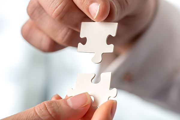 Two businesspeople fitting together matching interlocking puzzle pieces conceptual of teamwork and problem solving closeup of their hands.
